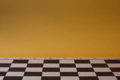 Wooden chess board with yellow empty background. Stock Photos
