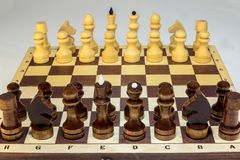 Wooden chess on a chessboard at the beginning of the game. stock photography