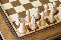 Wooden chess figures on a wooden   chessboard. Royalty Free Stock Photo