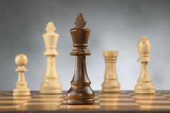 Wooden chess game pieces. Beautiful wooden chess pieces on wooden chess game board Royalty Free Stock Photo