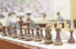 Wooden chess pieces. On the Board and the boy playing in the background Royalty Free Stock Image