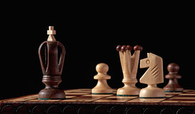 Wooden chess pieces on a board. Chess pieces made from wood on a wooden chess board in a studio setting Stock Images