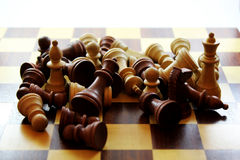 Wooden Chess Pieces and Board. Wooden chess pieces in a pile on a chess board Stock Photography