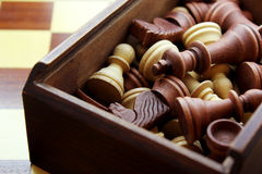 Wooden Chess Pieces in Box. Wooden box of chess pieces on inlaid checkered chess board Royalty Free Stock Photo