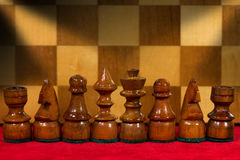 Wooden Chess Pieces with Chessboard. Macro photography of some wooden chess pieces on a red velvet with wooden chess board on the background Royalty Free Stock Photos