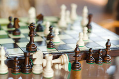 Wooden chess pieces on chessboard outdoor at the sunny day, at terrace house. Royalty Free Stock Image