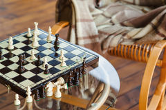 Wooden chess pieces on chessboard outdoor at the sunny day, at terrace house. Stock Photo