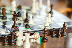 Wooden chess pieces on chessboard outdoor at the sunny day, at terrace house. Royalty Free Stock Photo