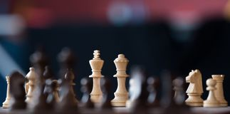 Wooden chess pieces on a chessboard Stock Photos