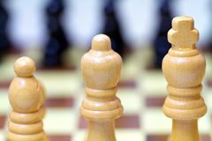 Wooden chess pieces. On first rank Royalty Free Stock Photography