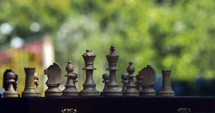 Wooden chess pieces on a wooden chessboard outdoor at the sunny Stock Photos