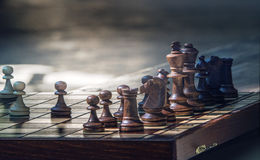 Wooden chess pieces on a wooden chessboard outdoor at the sunny Stock Images