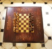 Wooden chess set circa 1930. Light and dark coloured hand carved wood chess pieces. The board is painted onto the table itself Royalty Free Stock Photos