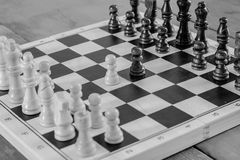 Wooden chess set fight, black and white photo. Stock Photo