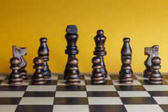 Wooden chess set yellow background. Royalty Free Stock Photos