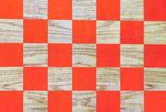 Wooden chessboard with orange cells. Checkerboard background stock photos