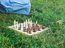 Wooden chessboard with white and brown figures lies on the grass in the park. Hobby, education, intellect. Ual game stock photos