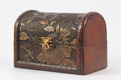 Wooden chest. With metal lock and beautiful carved flowers and leaves at the top and front royalty free stock photography
