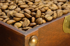 Wooden chest with coffee beans. Old brown wooden chest with coffee beans close-up Royalty Free Stock Image