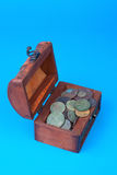 Wooden chest with coins inside. Isolated on blue Royalty Free Stock Image