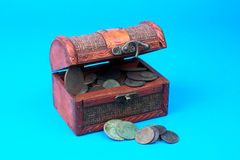 Wooden chest with coins inside. Isolated on blue Stock Photo