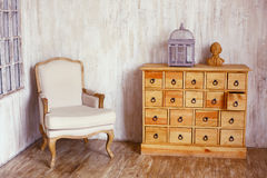 Wooden chest of drawers in shabby styled room with bird cage and Royalty Free Stock Photo