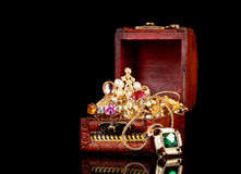 Wooden chest full of gold jewelry. On black background royalty free stock photography