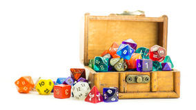 Wooden chest overflows with dice. A small wooden chest overflows with multicolored dice Stock Images