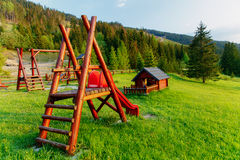 Wooden children playground in highland landscape and small cottage.. Royalty Free Stock Images