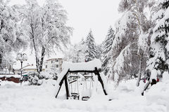Wooden children's swing covered by snow Stock Photos