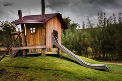 Wooden childrens playhouse with slide Royalty Free Stock Images
