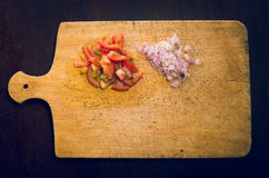 Wooden chopping board with chopped tomatoes and Royalty Free Stock Photography
