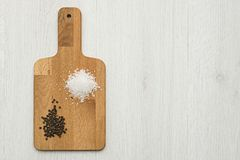 Salt and pepper. Wooden chopping board with natural salt and black pepper on table, with copy space royalty free stock image