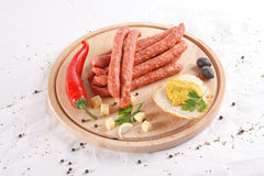 Wooden chopping board with sausages, cheese, bread Royalty Free Stock Image