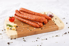 Wooden chopping board with sausages and spices Royalty Free Stock Photos