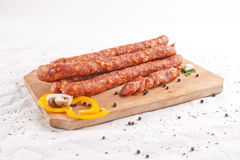 Wooden chopping board with sausages, vegetables an Stock Images