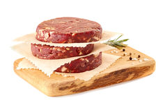 Wooden chopping board with stack of raw beef burger patties on white Stock Photography