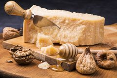 Tasty italian food on wooden chopping board. Wooden chopping board on which is disposed the ripened cheese, dried figs, walnuts and honey stock images
