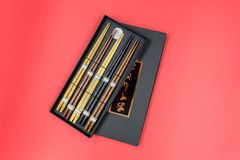 Wooden chopsticks on black box isolated on red background royalty free stock photos