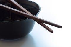 Wooden chopsticks on black dish. Stock Photo