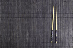 Wooden chopsticks on brown bamboo straw mat Royalty Free Stock Photography