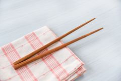 Wooden chopsticks kitchenware set on napery on dining table Zero waste use less plastic concept. Wooden chopsticks kitchenware set on napery on dining table / stock photos