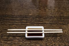 Wooden chopsticks lie on the dishes. With soy sauce.Copy space Stock Photos