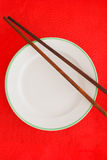 Wooden chopsticks on red background Stock Images