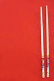 Wooden chopsticks on red. Fabric background Stock Photography