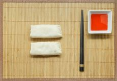 Wooden chopsticks, spring rolls and sweet and sour sauce on bamboo mat background. royalty free stock image