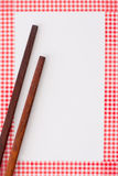 Wooden chopsticks. On white background and red checkered frame Stock Photos