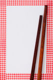 Wooden chopsticks. On white background and red checkered frame Stock Photo