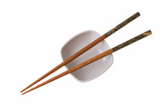 Wooden chopsticks on white saucer Royalty Free Stock Image
