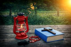 Wooden christian cross on bible, burning kerosene lamp and prayer beads on the old table. Salvation of soul and expiation of sins. Wooden christian cross on Royalty Free Stock Photo
